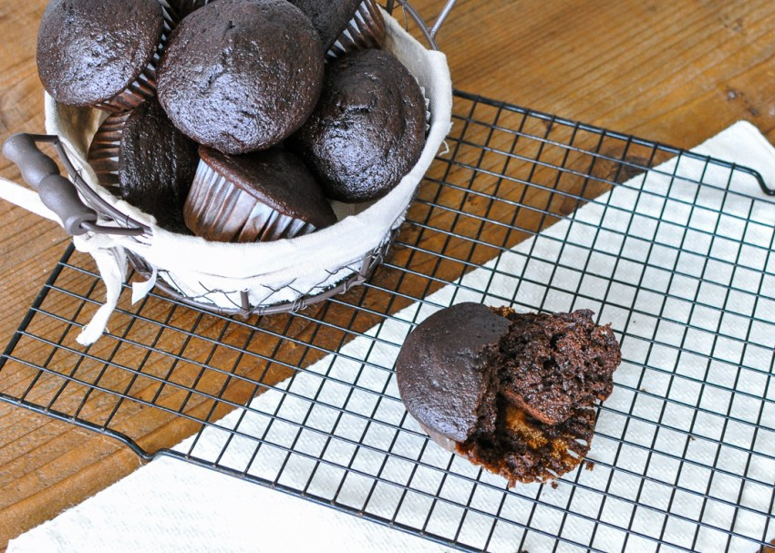 a horizontal picture of chocolate muffins in a basket sitting on a black rack against a brown wood background with a white napkin
