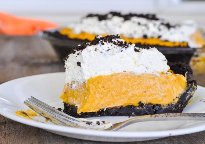A single slice of pumpkin no-bake cheesecake with oreo crust sitting on a white place.