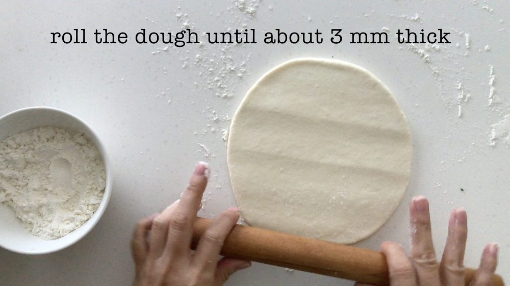 flattening a dough into a thin pancake with a rolling pin