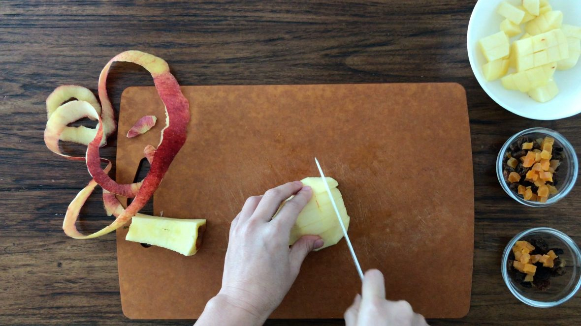 Cutting a peeled apple on a chopping board with some dried fruits on the side