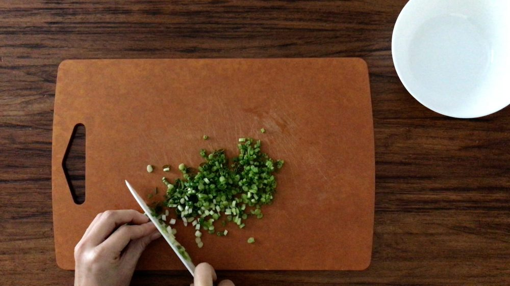 chopping scallions on a brown chopping board