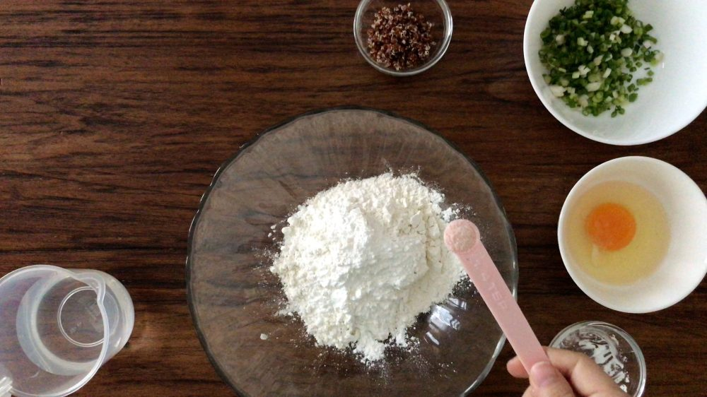 Adding some salt into a big glass bowl with flour inside
