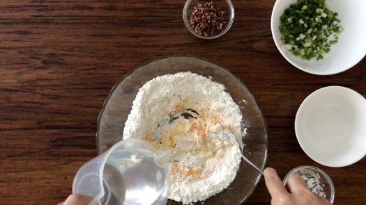 Pouring water in the mixture of egg and flour in a big glass bowl