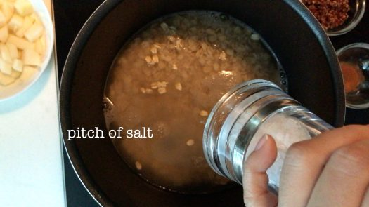 adding some sea salt into a pot with rolled oats and water inside