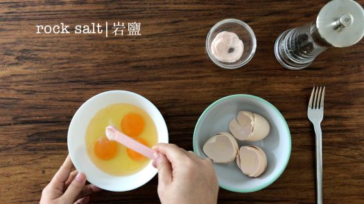 put a some salt into a bowl of eggs with a pink tea spoon