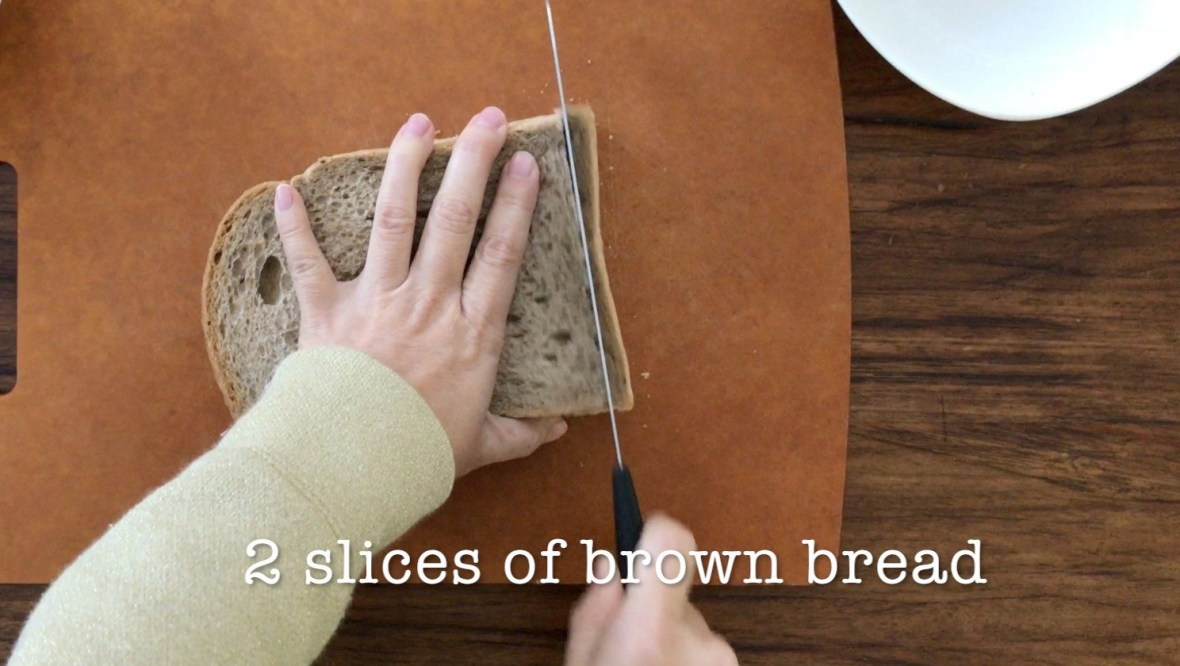 Cutting off the crust of two pieces of sliced brown bread