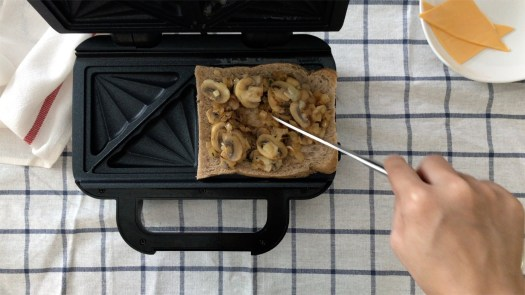 Putting sauteed mushrooms on top of a slice of brown bread in the toasties maker