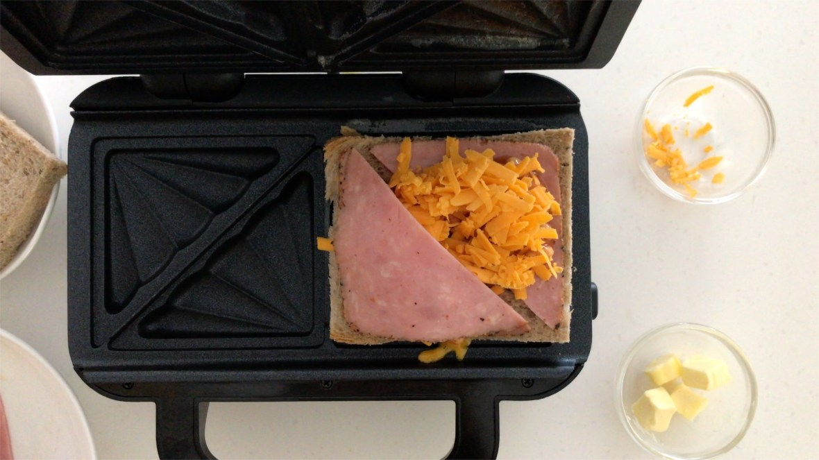 Putting some grated Cheddar cheese on the toasties and lay another layer of ham on top