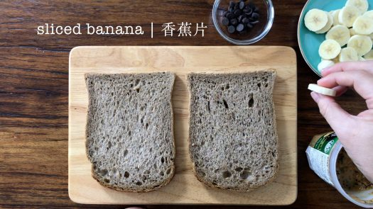 Banana peanut butter sandwich ingredients are sliced banana, two pieces of brown bread, peanut butter and dark chocolate chips