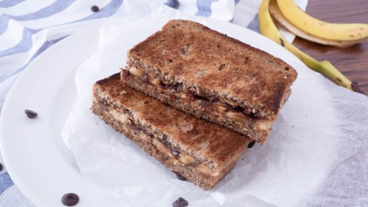 halved grilled banana peanut butter sandwich serving on a white plate
