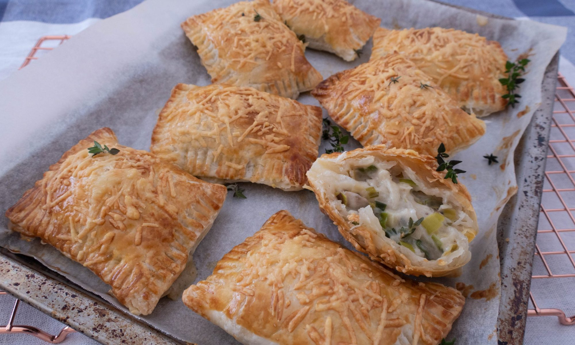 8 crispy golden brown mushroom and leek puff pastries in a baking tray and one of the pastry is cut in half to reveal the mushroom and leek stuffing inside