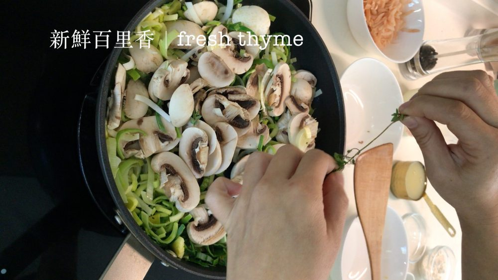 Picking fresh thyme leaves and put them into a pan with sliced mushrooms and chopped leek
