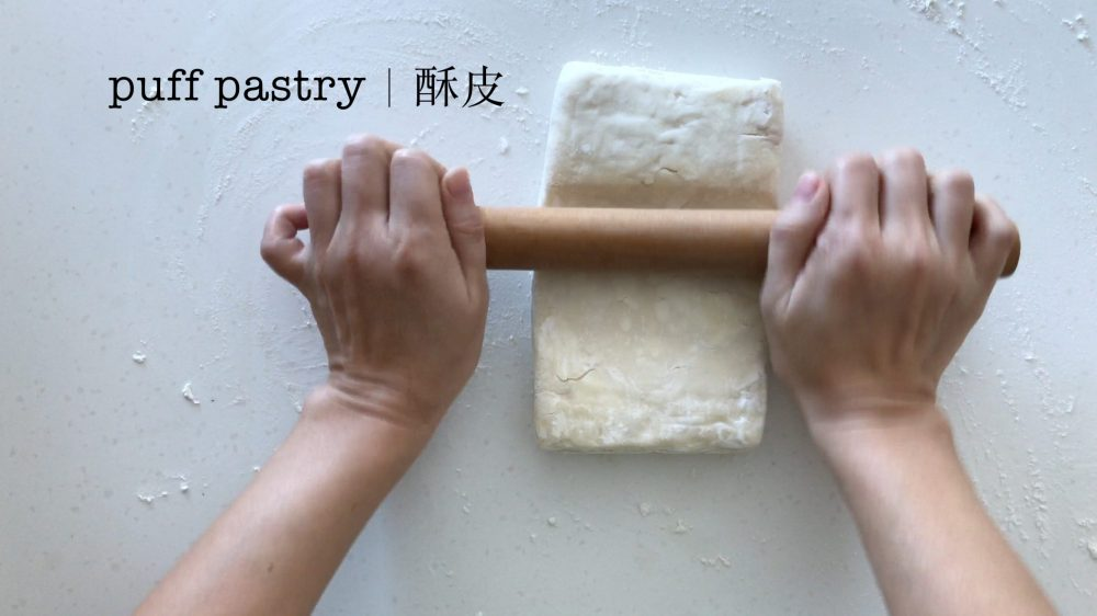 flattening puff pastry with a rolling pin