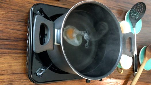 The egg sinks at the bottom of the pot and form a oval shape