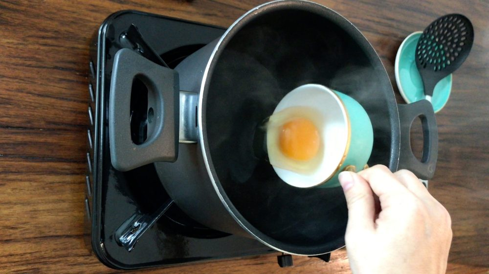 Pouring an egg into a pot of hot water