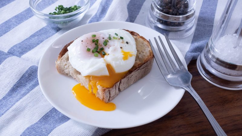Egg yolk coming out from a poached egg on a piece of toast.