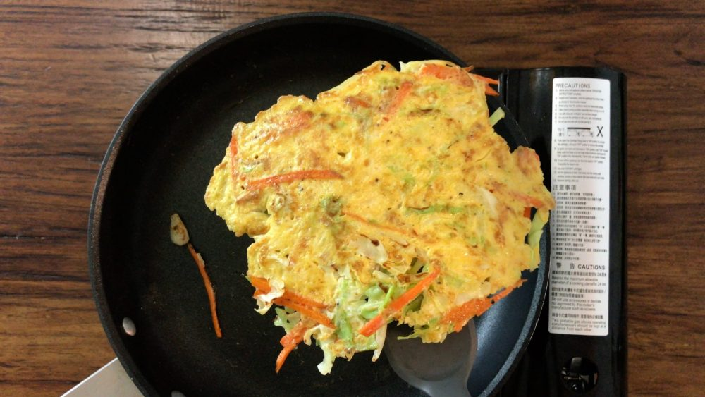 Making a pancake with mixed vegetables and egg
