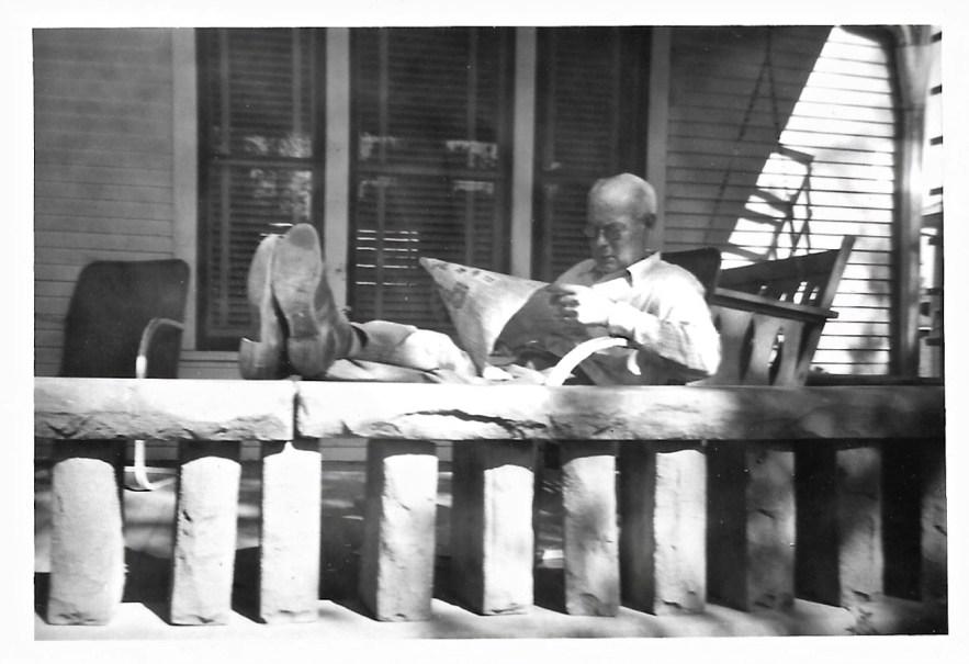 W. W. Phillis reading paper on front porch