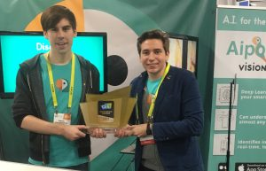 Simon and Alberto, Aipoly founders, holding a golden trophy from the Consumer Electronics Show, in an Aipoly themed booth with teal colors and the parrot logo. They are smiling and look exhausted