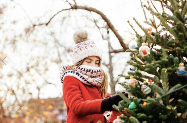 Girl putting Christmas decoration on tree