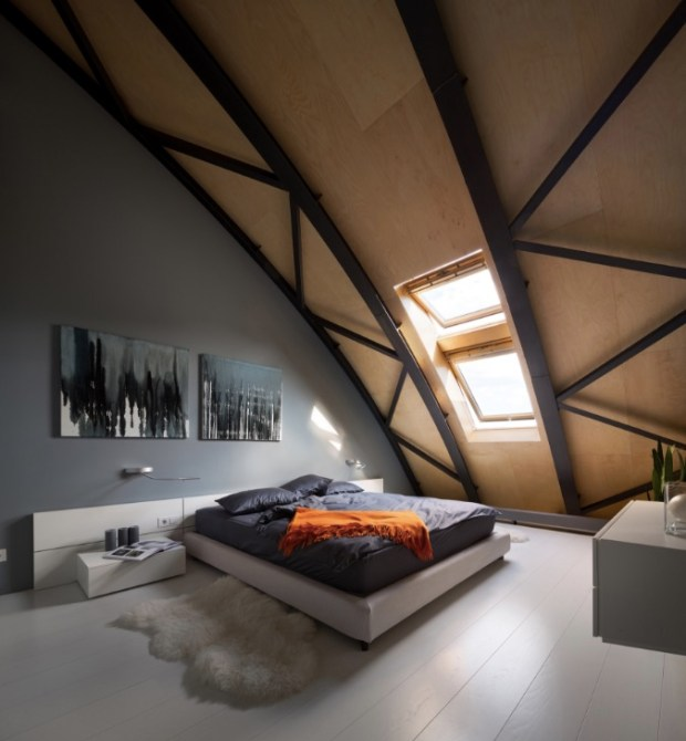 Bedroom in a modern loft apartment, formerly a commercial building, with an arcing steel beam roof line in Kiev, Ukraine