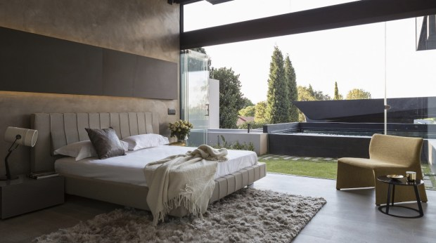 Modern bedroom opens onto private pool area through folding glass doors in this home in Johannesburg, South Africa