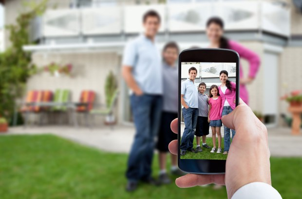 Person Hand Using Mobile Phone For Taking Family Photo