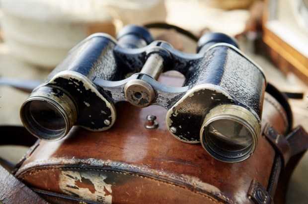 pair-of-vintage-binoculars-with-a-worn-leather-case-at-a-flea-market