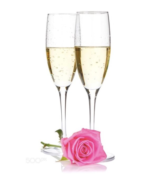 Two champagne glasses and pink rose flower