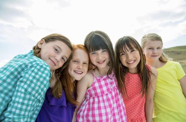 Portrait of happy schoolgirls standing together