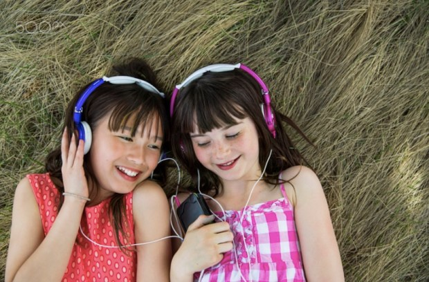 Smiling girls lying on hay listening to music