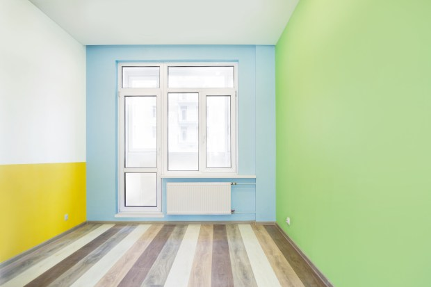 Empty cheerful kids room with green, yellow and blue color walls and wooden flooring after renovation