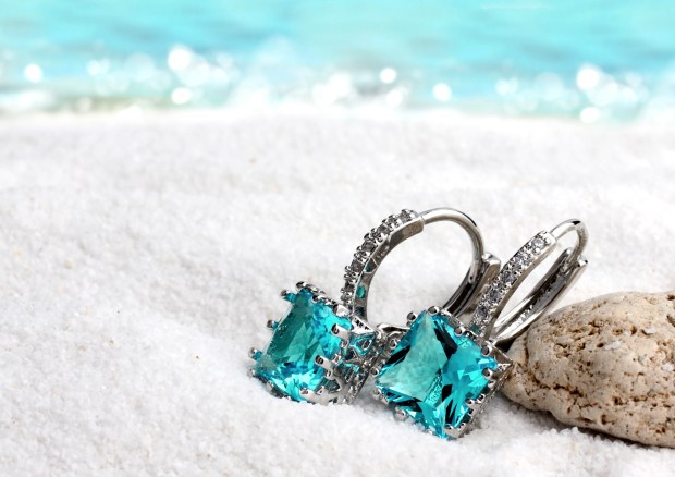 Jewelry earrings with aquamarine on sand beach background, soft focus