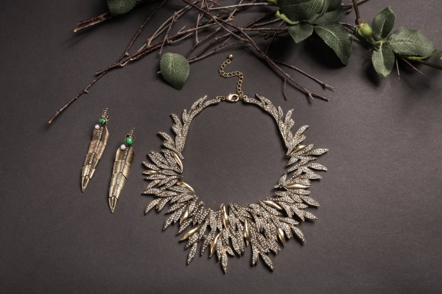 Leaves shape golden necklace and earrings set with tree leaves setup on black background