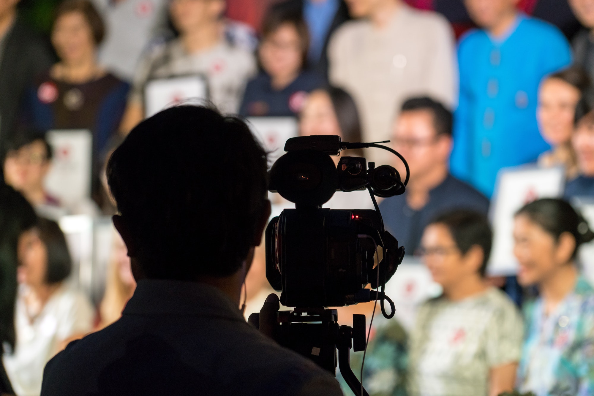 Silhouette of camera man from behind with audience of many men and women sitting blurred in the