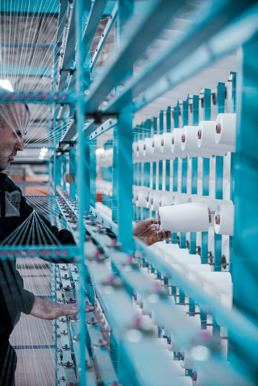 man in black jacket standing beside blue metal machine