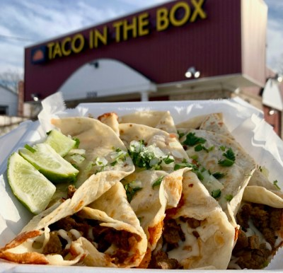 a container with three giant tacos with cilantro and lime in front of the restaurant drive through of taco in the box