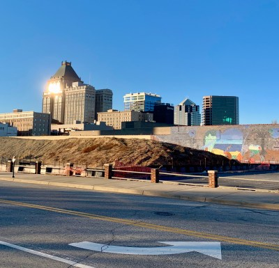 an image of downtown greensboro from the train depot with a traffic turning arrow that looks like a smile and the glint of sun off a building in the distance that looks like a winking eye