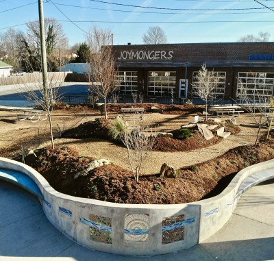 looking toward joy mongers brewery from lofi park with new permaculture plantings and tile concrete wall looking on from the intersection