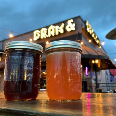 two mason jars of mixed drink sit on a wooden railing with dram and draught sign in the background