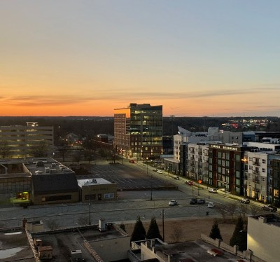 a view of project slugger building from atop a parking deck in downtown greensboro at sunset