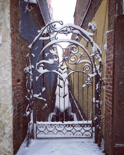 snow on a metal gate between brick buildings and a narrow alley with water fall