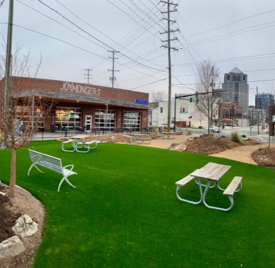 a photo of lofi park in greenboro with turf grass laid near joymongers brewery picnic tables and a bench are on the turf grass