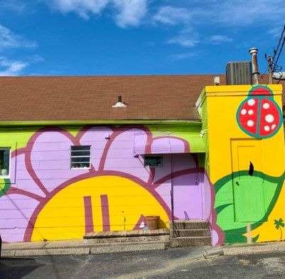 a mural of a sunflower and a lady bug on the back of the tiny greenhouse shop in greensboro nc