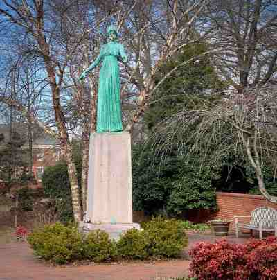 the statue of minerva on the campus of uncg with apples and offerings placed on its pedestal.