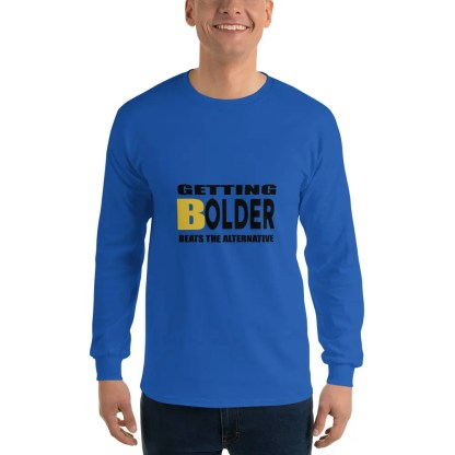 Man with a smile is wearing dark jeans & a long sleeved royal t shirt with the slogan getting bolder beats the alternative