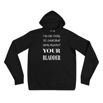 A black hoodie lying flat on a white background with a slogan in white which says the one thing to shrink during pregnancy your bladder