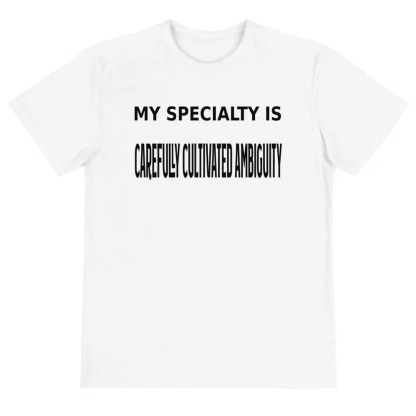 A white short sleeved t shirt lying flat on a white background with a slogan in black which says my specialty is carefully cultivated ambiguity