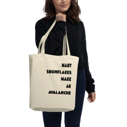 A smiling woman dressed in dark colors holding a beige tote bag in front of her with the slogan many snowflakes make an avalanche