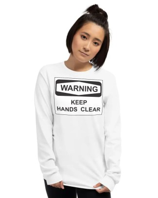Smiling woman wearing dark jeans , short, straight hair in a ponytail & long sleeve white t shirt with black & white slogan graphic saying warning keep hands clear